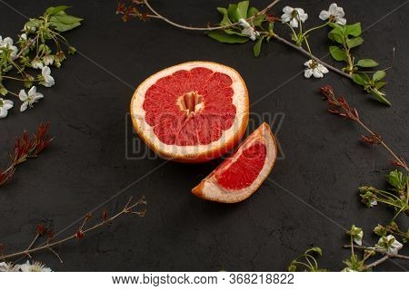 A Top View Sliced Grapefruit Mellow Juicy Ripe Isolated Along With White Flowers On The Dark Backgro