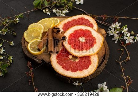 A Front View Citruses Sliced Lemon And Grapefruit Fresh Mellow Ripe On The Brown Wooden Desk And Gre