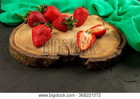 A Front View Red Strawberries Sliced Mellow Ripe On The Brown Desk On The Dark Background