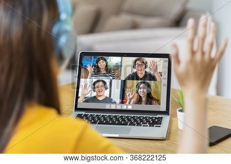 Rear View Of Asian Business Woman Say Hello With Teamwork Colleague In Video Conference When Coronav