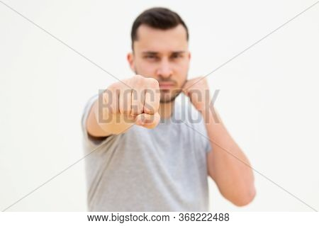 Attractive Man In Grey T-shirt Tightening Fists And Punching. Concentrated Caucasian Guy Training An