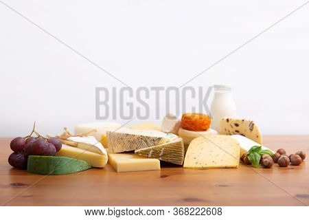 Assorted Sliced And Whole Cheeses, Bottle Of Milk, Macadamia Nuts And Grape Bunch On Wooden Table. D