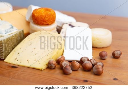 Assorted Cheeses, Whole Blocks And Slices, And Macadamia Nuts On Wooden Table. Top View. Healthy Foo