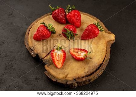 A Top View Red Strawberries Sliced Ripe Mellow On The Brown Desk On The Dark Floor