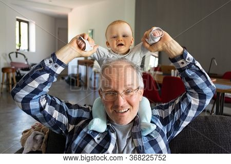 Grandfather Smiling While Lovely Baby Sitting On His Shoulders And Holding Grandchild Hands. Adorabl