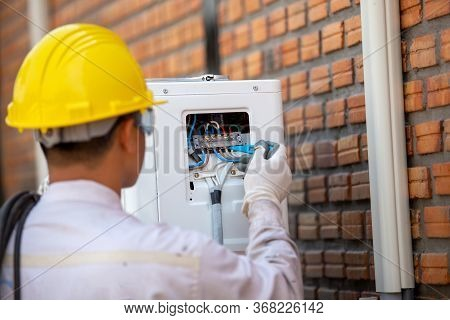 The Air Conditioner Technician Checks The Electrical Power Of The Air Conditioner Compressor From Th