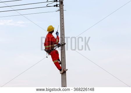 Uniformed Electricians Work On High-rise Electricity Poles Along With Safety Equipment And Radio Com