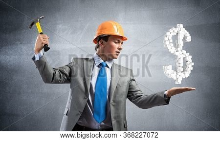 Businessman Going To Crash With Hammer Dollar Symbol. Young Handsome Man In Business Suit And Safety