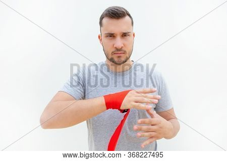Frowning Man Removing Protection After Boxing Or Fighting. Guy With Bristle Unwrapping Hand After Tr