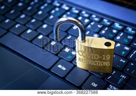 Covid-19 Coronavirus Lockdown Restrictions Ease Concept Illustrated By Unlocked Padlock On Laptop.