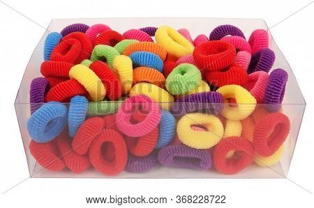 Rubber bands for hair colorful pile in transparent box on white background