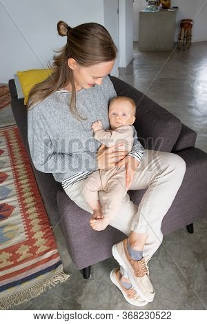 Positive Young Mom Leaning On Couch At Home, Rocking Baby In Arms, Soothing Little Daughter. Vertica