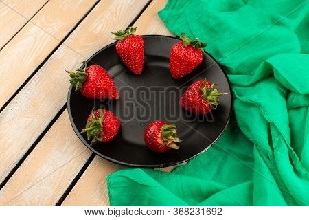 A Top View Red Strawberries Mellow Juicy Fresh Inside Black Plate On The Brown Wooden Floor