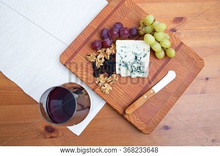 Glass Of Wine, Slice Of Blue Cheese, Nuts, Grapes And Knife On Wooden Chopping Board. Top View. Cele