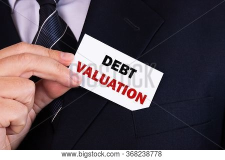 Businessman Put Card With Text Debt Valuation In Pocket. Business Concept.