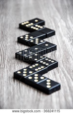 Black Domino Dice On A Light Wooden Table, The Process Of Playing Dominoes, Selective Focus, Close U
