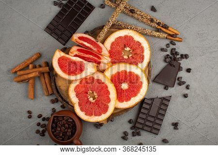 A Top View Sliced Grapefruits Mellow Along With Choco Bars And Cinnamon On The Grey Background