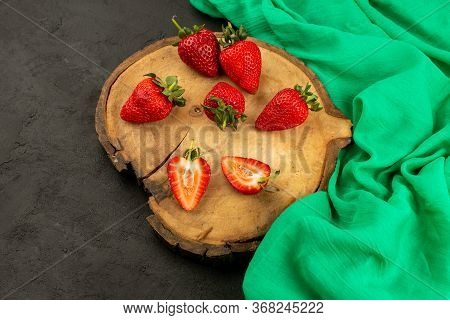A Front View Fresh Strawberries Red Ripe Mellow Sliced And Whole On The Brown Wooden Desk On The Gre