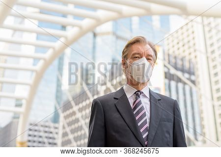 Mature Businessman With Mask For Protection From Corona Virus Outbreak At Skywalk Bridge