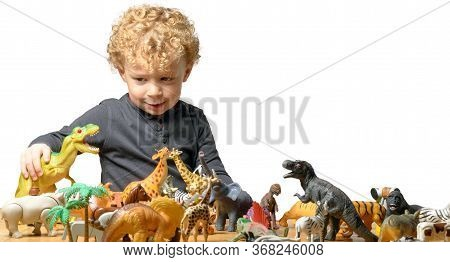 A Little Child Plays With Toys Animals And Dinosaur