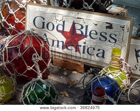 God Bless America distressed sign set in a coastal theme with netting and colored glass balls poster