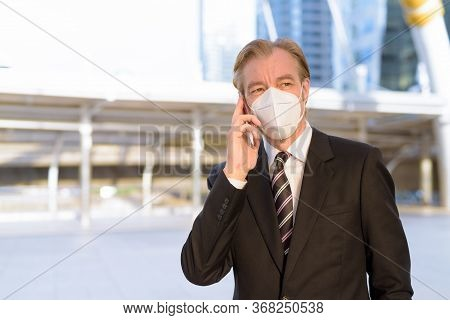 Mature Businessman With Mask Thinking While Talking On The Phone At Skywalk Bridge