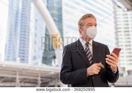 Mature Businessman With Mask Thinking While Using Phone At Skywalk Bridge