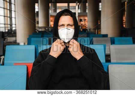 Men In Respirator Mask N95 Sitting At The Empty Airport Terminal. Coronavirus Covid-19 And Air Pollu