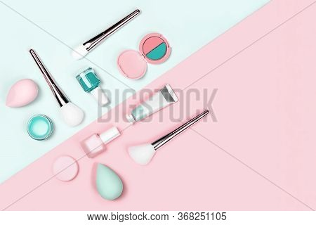 Makeup Products With Brushes, Nail Polish, Eyeshadow, Sponges, Cream And Lipstick On Neo-mint And Pi