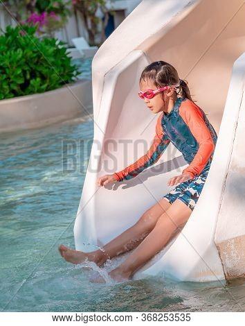 Little Girl Is Sliding Down The Water Slide In Aqua Park Children Playground.