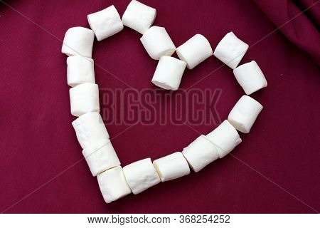 Marshmallows Laid Out In The Shape Of A Heart Isolated On A Pink Background. Bunch Of Small White Ma