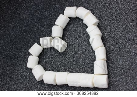 Marshmallows Laid Out In The Shape Of A Heart Isolated On A Gray Stone Background. Bunch Of Small Wh