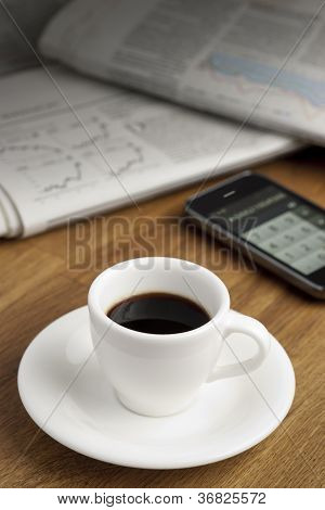Coffe cup, smartphone and newspapers.