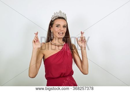 Young Attractive Brunette Woman In Red Stylish Dress, With A Crown On Head On White Background, Fema