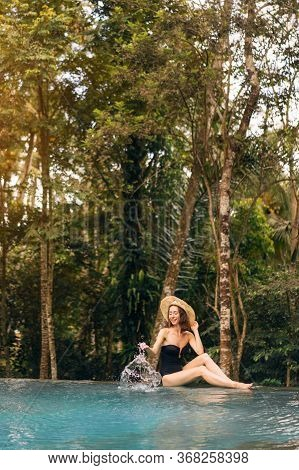 Happy Young Woman Sitting On The Edge Of A Swimming Pool In Jungle, Wearing A Black Swimsuit And Str