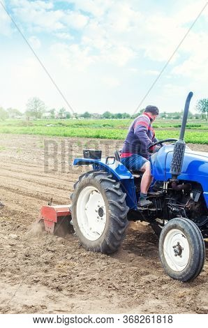 A Farmer On A Tractor Cultivates A Farm Field. Soil Milling, Crumbling And Mixing. Loosening The Sur