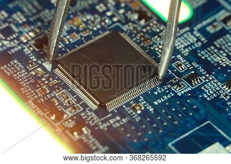 Master Picks Up The Microchip Close-up With Tweezers. Close-up Of An Electronic Circuit Board With M