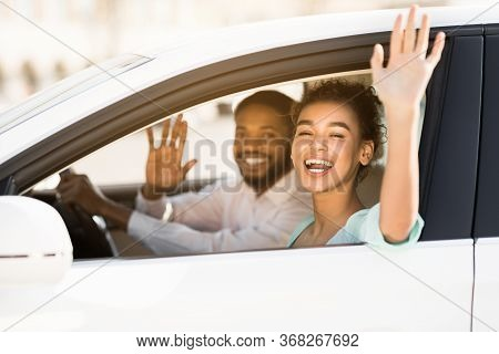 Good Bye. Joyful African Couple Waving Hands Sitting In Car Having Road Trip On Vacation. Selective