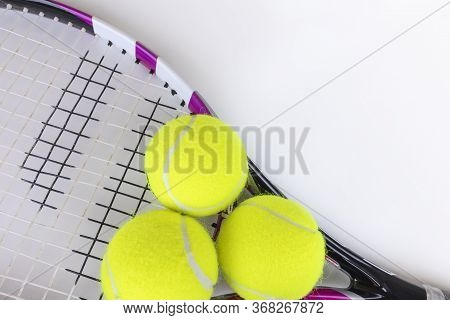 Tennis Racquet And Three Balls With Copyspace Top View Onwhite Background. Playing Tennis Equipment.