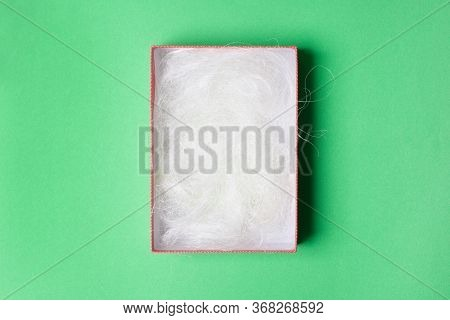 Opened Light Green Box With Filling Material On Green Colored Paper Background.