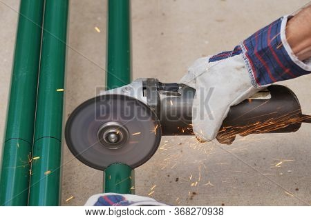 An Angle Grinder With Cutting Disc For Steel Is In Use. Cutting Steel Pipes.
