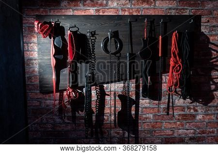 A Set Of Varied Leather Lashes For Sexual Pleasures Hang On A Wooden Hanger On A Brick Wall. Sex Equ