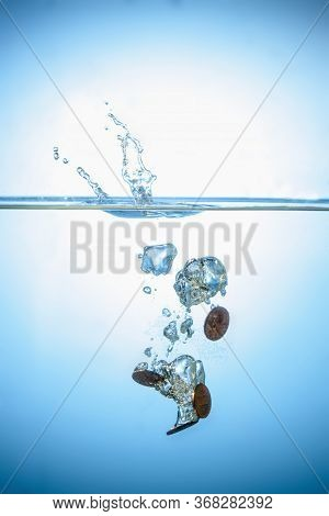 Coins Falling And Splashing Into Water As A Symbol Of Profit In Business And Implementing A Strategi