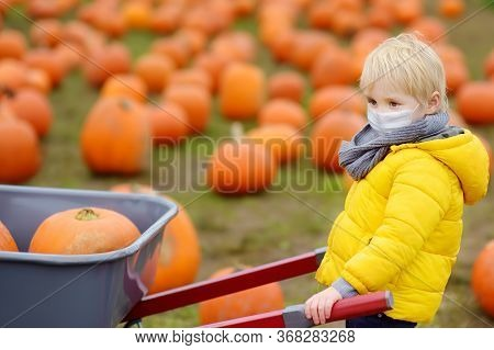 Little Boy Wearing Face Mask And Keeping Social Distancing On Tour Of Pumpkin Farm At Autumn. Kid Ca