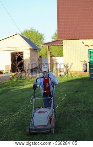 Moscow Russia-may 2020: Little Boy Rides Piggy Back While Dad Mows The Familys Front Yard. Dad Is Gr