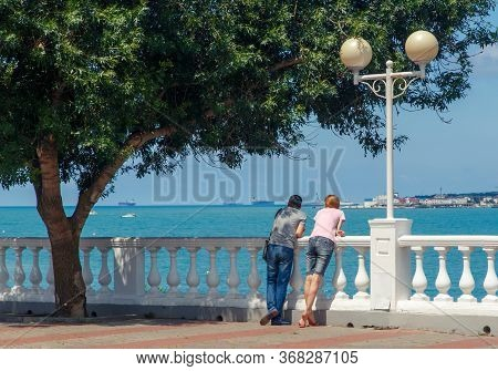A Young Couple-a Man And A Woman, Stand On The Embankment Of The Resort Of Gelendzhik Under A Green