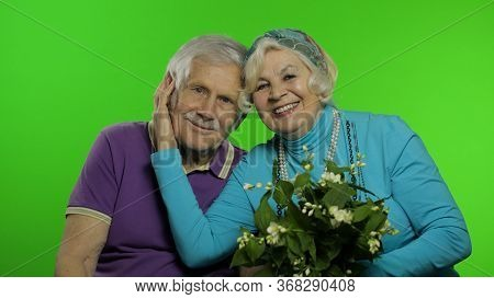 Senior Aged Retired Couple Man And Woman Grandparents. Grandfather And Grandmother With Bouquet Of F