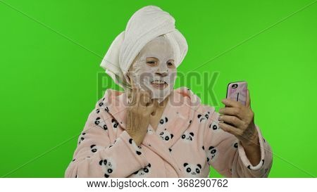 Adult Senior Caucasian Woman Grandmother In Bathrobe And Cosmetic Fabric Face Mask On Face Making Se