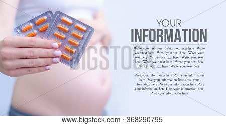 Pregnant Woman Holding Vitamins For Pregnant On Gray Blur Background, Space For Text