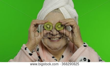Adult Senior Caucasian Woman Grandmother In Bathrobe And Bubble Face Mask With Two Halves Of Kiwi Ap